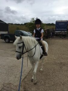 Kelly Tilbrook's daughter on her white pony